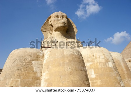 The Great Sphinx of Giza is a statue of a reclining lion with a human head that stands on the Giza Plateau on the west bank of the Nile, near Cairo. It is the largest monolith statue in the world. - stock photo