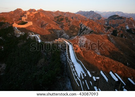 The Great Wall in winter. Red color in the sunshine. - stock photo