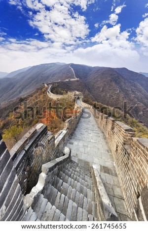 The Great Wall of China vertical day time panorama from stone tower top towards distant chain of fortification segments, stairways and towers in autumn mountains - stock photo