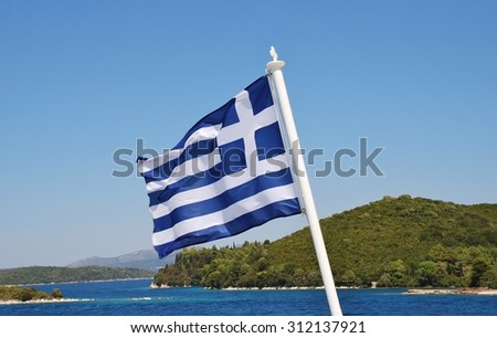 The Greek national flag flying from the stern of a ferry boat crossing between Lefkada and Meganissi islands in Greece. - stock photo