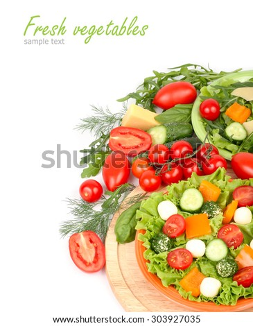 The Greek salad with cheese balls on an orange plate and fresh ripe vegetables and herbs on a white background with a place for the text. - stock photo