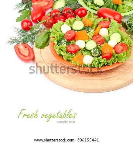 The Greek salad with cheese balls on an orange plate on a red checkered napkin and fresh ripe vegetables and herbs on a white background with a place for the text. - stock photo