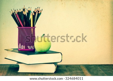 the green apple with pencil box on wooden table in concept of study or back to school with concrete wall background, retro and vintage color tone - stock photo