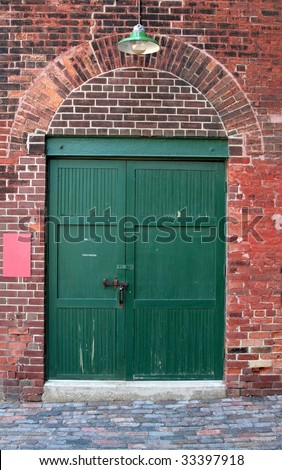 The green door of an old red brick warehouse.