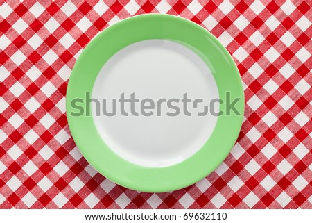 the green plate on checkered tablecloth - stock photo