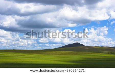 The green silky meadow and blue cloudy sky - stock photo