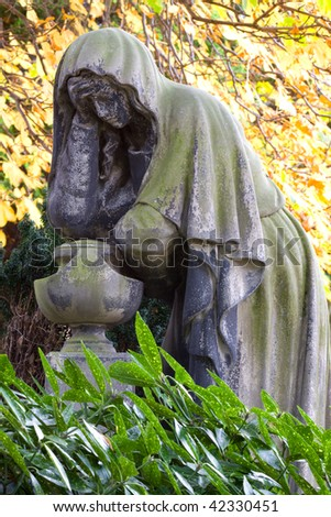 The Grieving Lady Monument. This beautifully rendered sculpture stands in an Edinburgh cemetery half-hidden in shadows and undergrowth. In this quiet corner she has mournednfor nearly two centuries. - stock photo