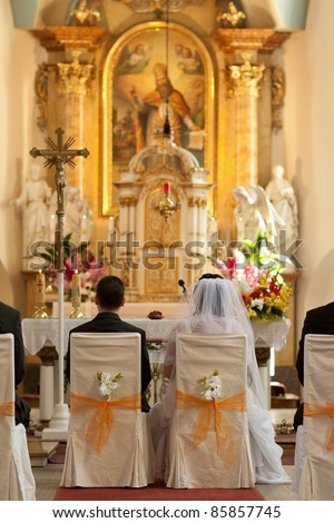 The groom and bride at the wedding ceremony in beauty church - stock photo