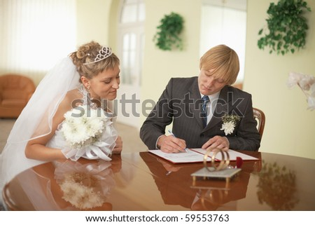 The groom and the bride at the moment of solemn registration of marriage - stock photo