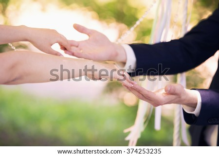 the groom and the bride hold each other by hands
