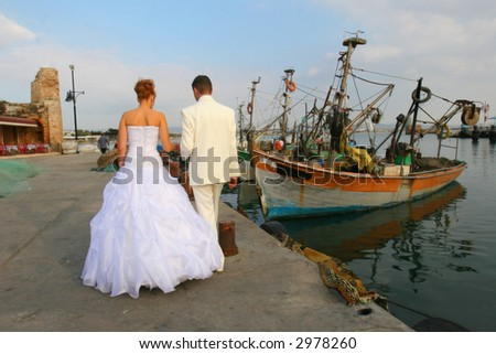 The groom and the bride walk in port - stock photo