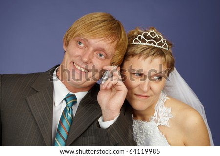 The groom calls on a cell phone, and the bride overhears - stock photo