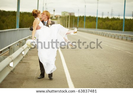 The groom carries his bride in his arms on the bridge - stock photo