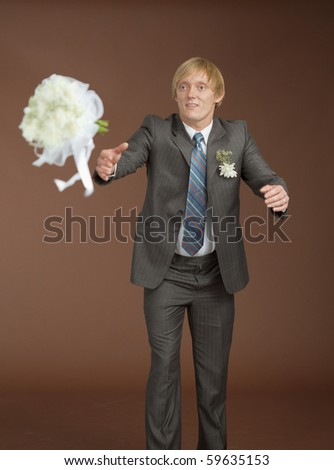 The groom catches a flying bouquet on a brown background - stock photo