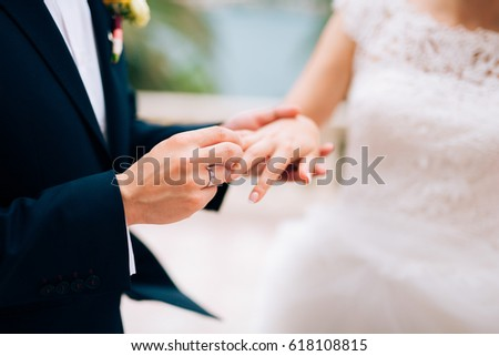 The groom dresses a ring on the finger of the bride at a wedding ceremony. Wedding in Montenegro.