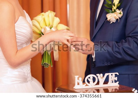 the groom dresses not weight a ring on a finger on wedding registration - stock photo