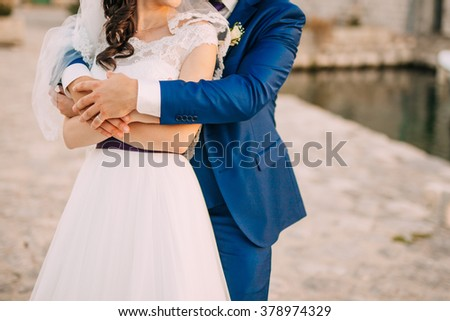 The groom embraces the bride - stock photo