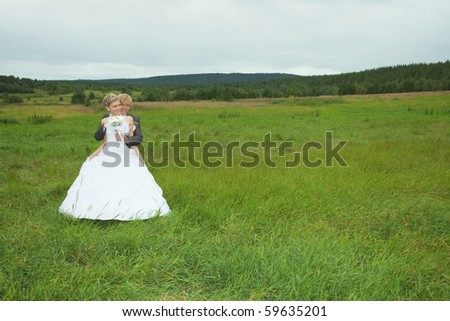 The groom embraces the favorite bride in a green field - stock photo