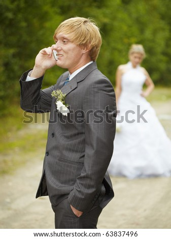 The groom has turned away from the bride and speaks on the phone - stock photo