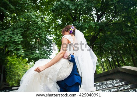 The groom holds his beautiful and happy bride in his arms - stock photo