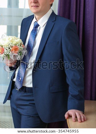 the groom in a dark suit with a wedding bouquet of red and beige color on the background of Windows and curtains in the room