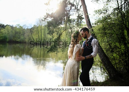 the groom in a wedding suit and the bride in lace dress with bouquet and wreath in the forest by the lake - stock photo