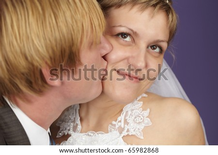 The groom kisses the bride on a purple background - stock photo