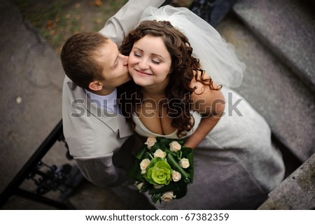 the groom kisses the bride on the cheek with a high angle