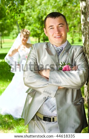 The groom near a tree and the bride on a background