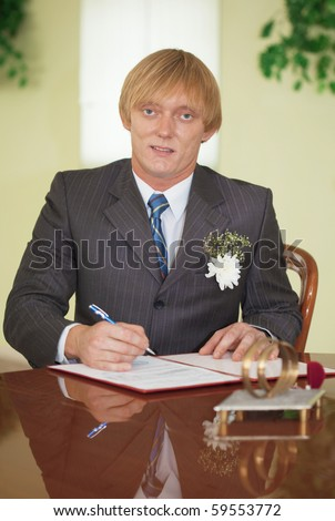 The groom puts his signature on the registration document - stock photo