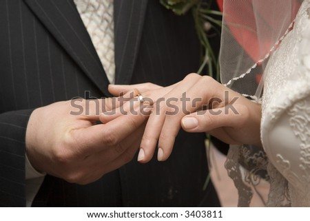 The groom puts on a wedding ring to finger of the beloved - stock photo