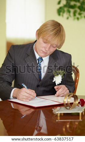 The groom solemnly signed wedding documents - stock photo
