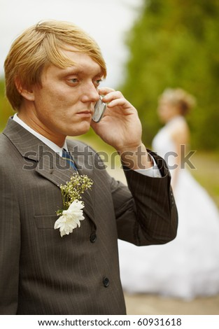 The groom speaks by phone having forgotten about the bride - stock photo