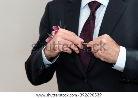 The groom wears a suit in front of a mirror. A elderly man ties a tie. An old groom preparing for the wedding. Wedding dress code clothing. Men's tie.  - stock photo