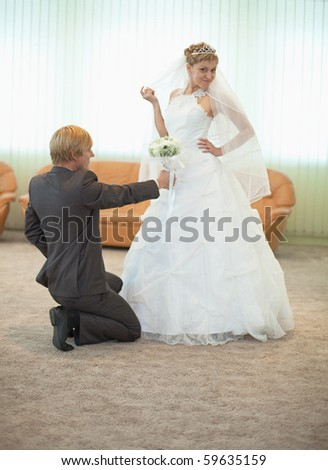 The groom with the bride funny pose in a ceremonial  hall - stock photo