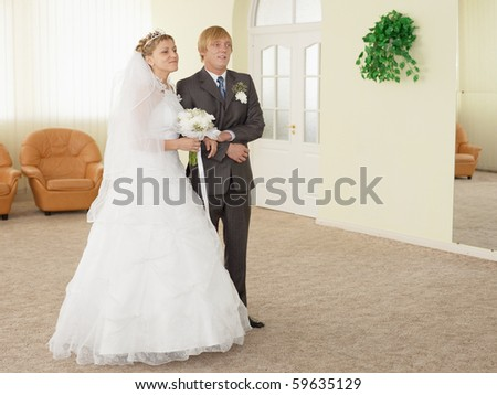 The groom with the bride in a ceremonial hall during wedding - stock photo