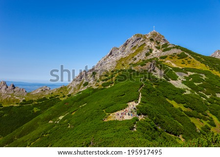 The group of hikers on mountain trail in Tatra Mountains, Poland. - stock photo