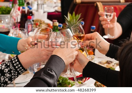 The group of people drinks alcoholic drinks on a banquet. - stock photo