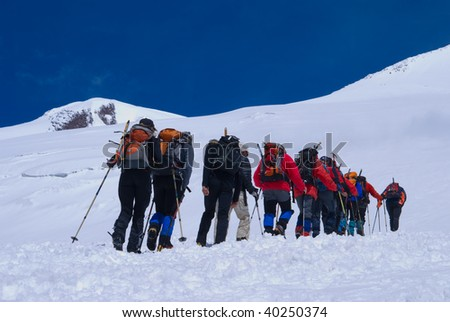 The group of rock-climbers accomplishes an ascent on the highest top of Europe - mountain El'brus, on Caucasus - stock photo