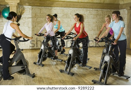 The group of women training on exercise bike at the gym with instructor.