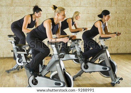 The group of women training on exercise bikes at the gym. Side view.