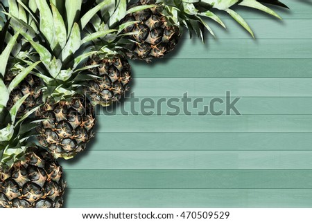 The Groups of Pineapples lying on green wood background.
