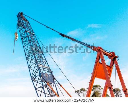 The grunge construction crane for heavy lifting is working in construction site and clear blue sky day.  - stock photo