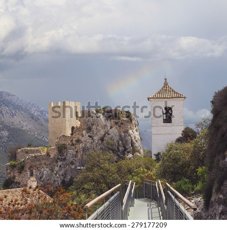 The Guadalest Fort and Chapel Tower With a Rainbow in the Background, Alicante, Spain - stock photo