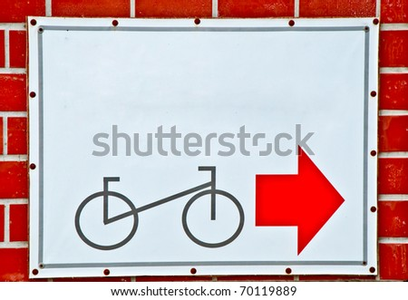 The Guide post park bicycle with red arrow on brick wall background - stock photo