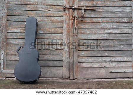 The guitar case rest on a gate. - stock photo