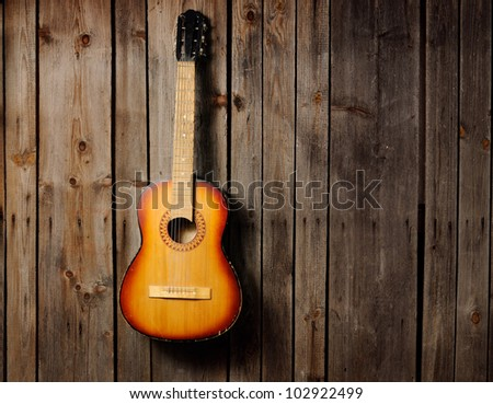 The guitar hanging on the old wooden wall - stock photo