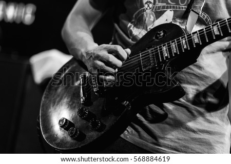 The guitarist is playing guitar , guitar background , music background , black  and white guitar