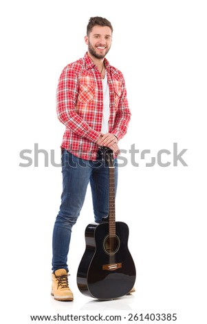 The guitarist. Man in red lumberjack shirt posing with a black acoustic guitar. Full length studio shot isolated on white. - stock photo
