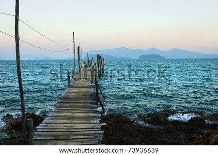 The Gulf of Thailand at dusk, wooden pier on turquoise water and islands on the horizon